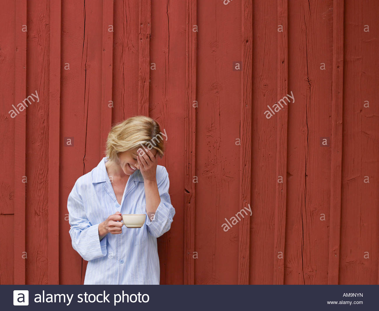 Woman with mug standing in front of red wall laughing. - Stock Image