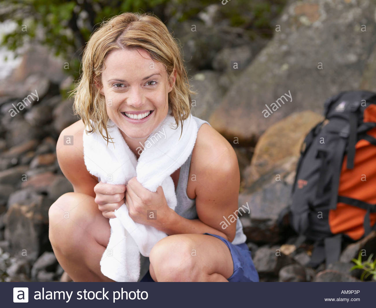 Woman crouching on rocks smiling with backpack in background. - Stock Image