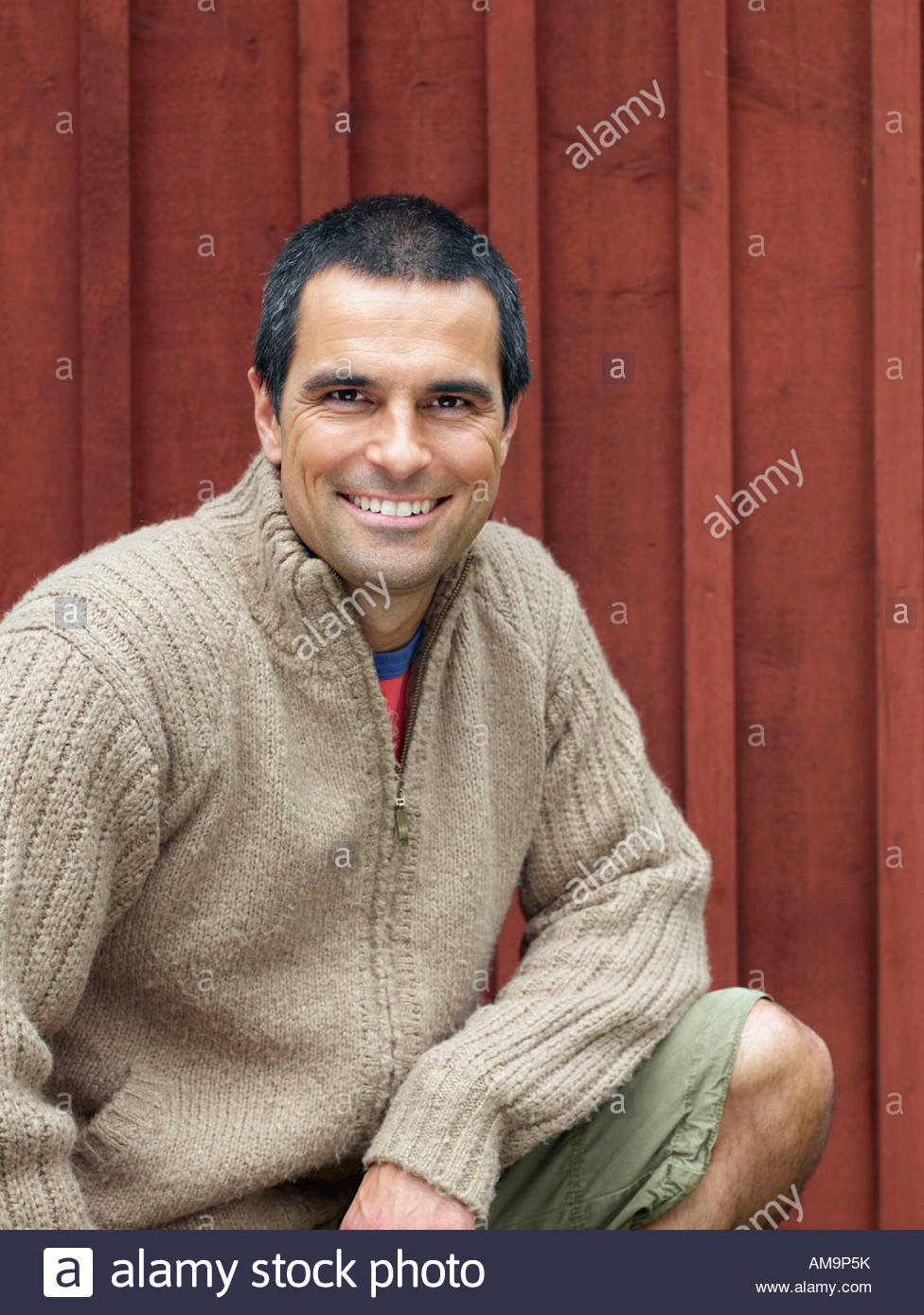 Man crouching in front of red wall smiling. - Stock Image
