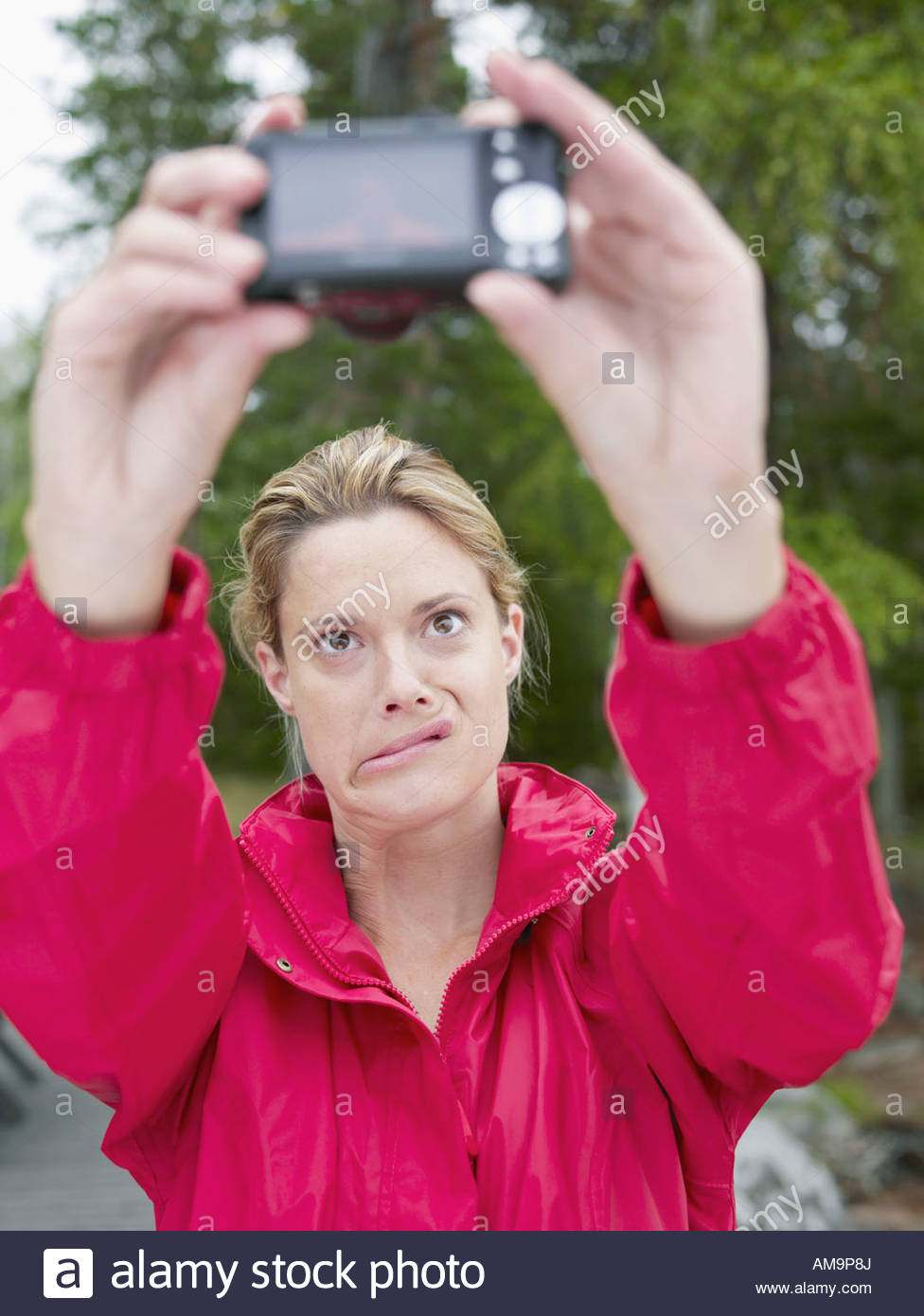 Woman taking self-portrait outdoors. - Stock Image