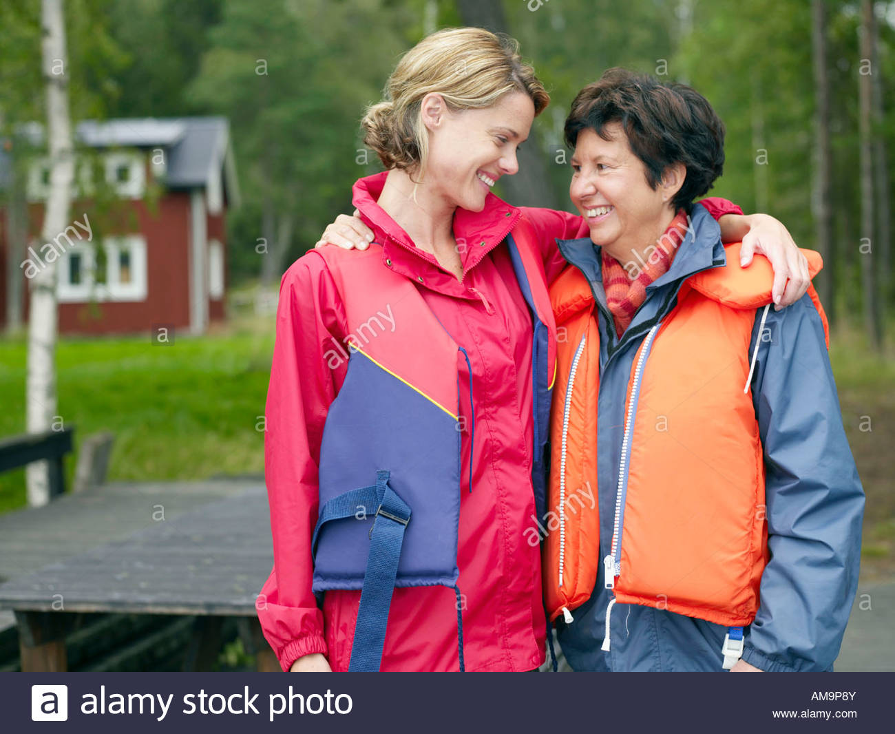 Two women standing together smiling with house in background. - Stock Image