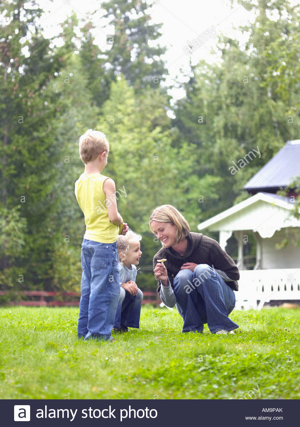 Woman with young girl and young boy in yard picking flower smiling. - Stock Image
