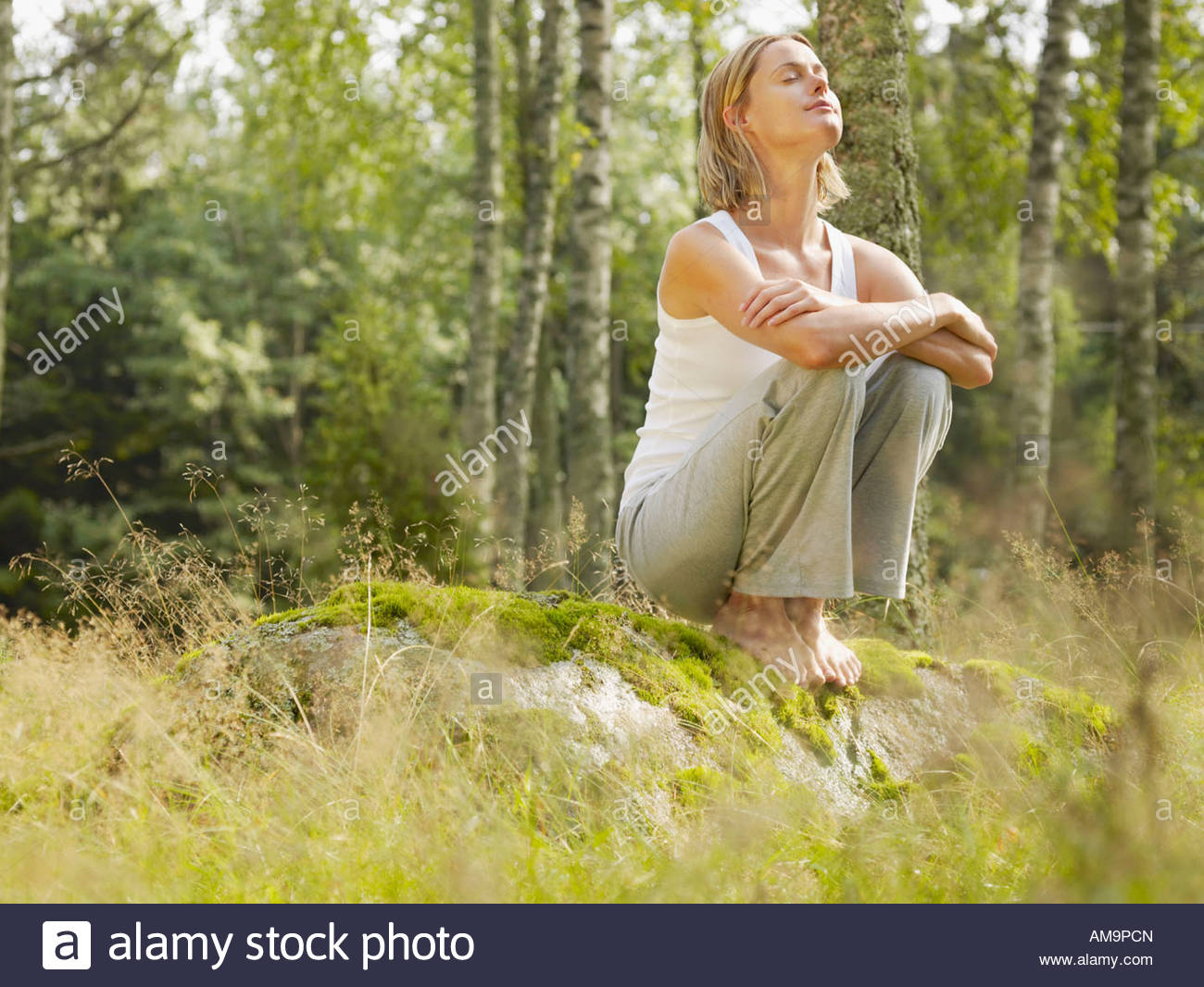 Woman crouching on a large rock in forest with eyes closed. - Stock Image