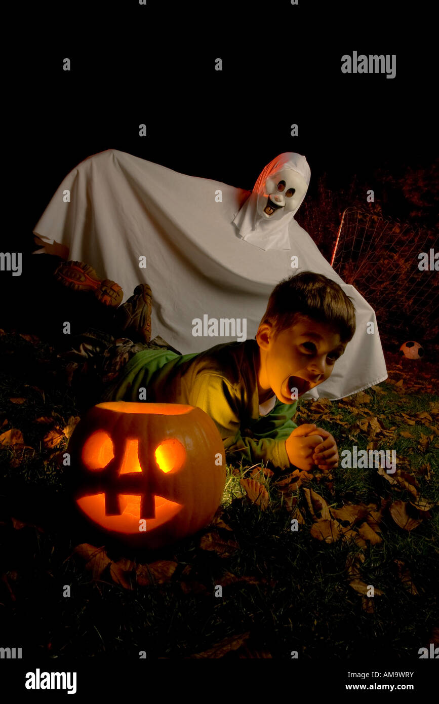 a young boy is given a fright on Halloween by a costume ghost next to his glowing pumpkin - Stock Image