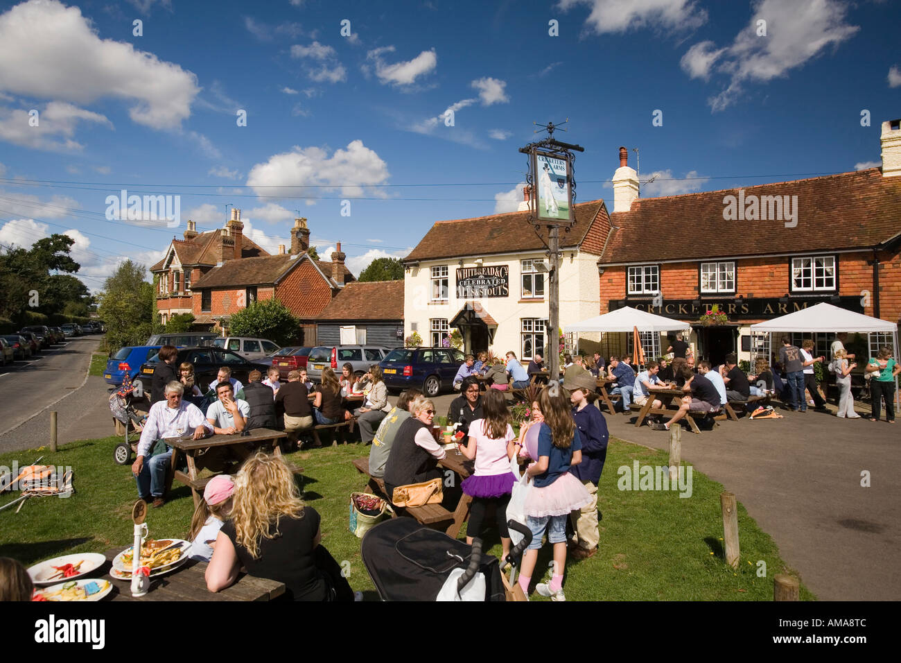 UK West Sussex Wisborough Green drinkers outside The Cricketers Village Pub in sunshine - Stock Image