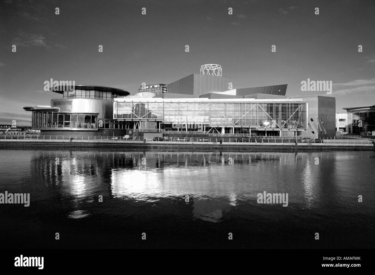 B&W lowry centre late afternoon with reflection in canal water salford quays manchester england uk europe - Stock Image