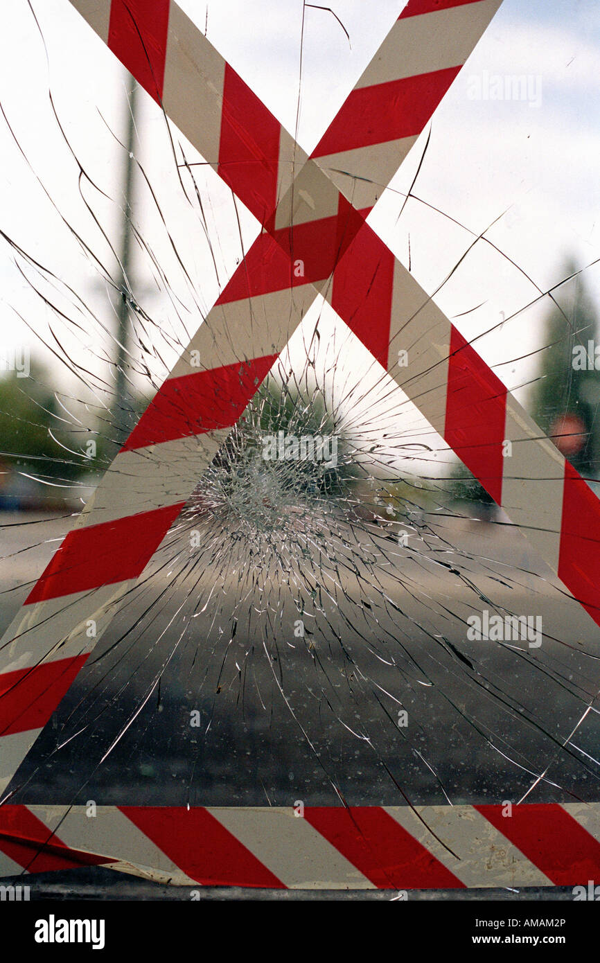 Striped tape on a shattered window - Stock Image