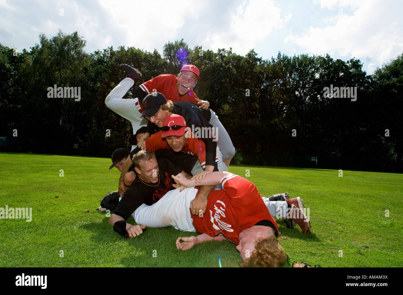 A baseball team piled on top of one another - Stock Image