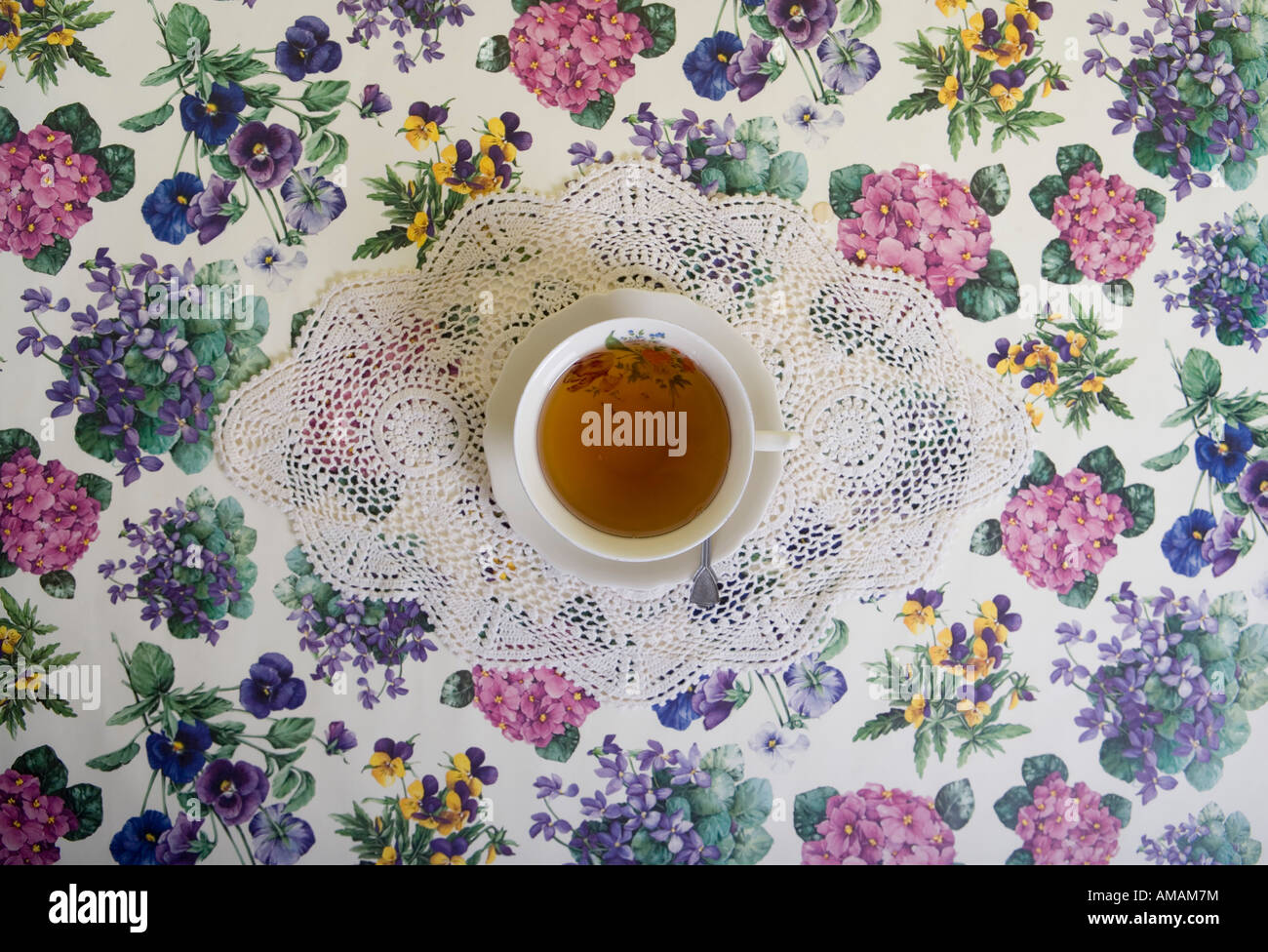 A cup of tea on a floral tablecloth - Stock Image