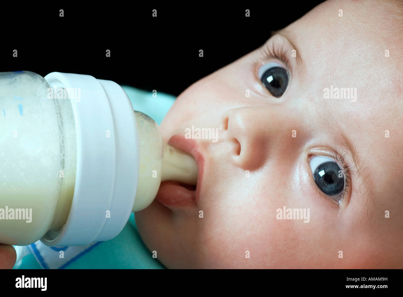 A baby drinking from a bottle - Stock Image