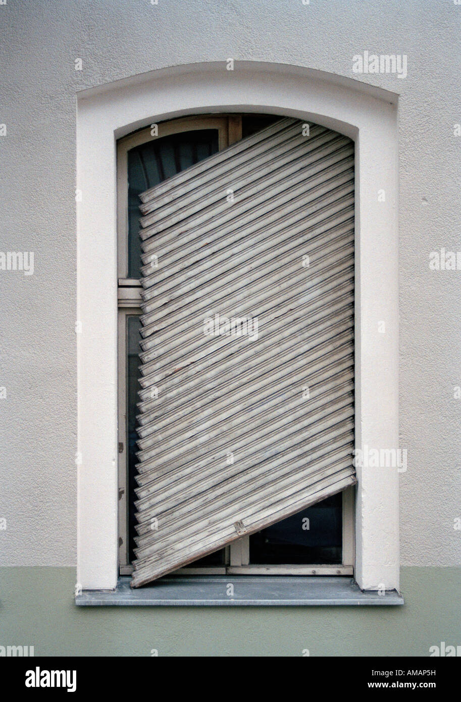 A broken shutter hanging at slanted angle on a window - Stock Image