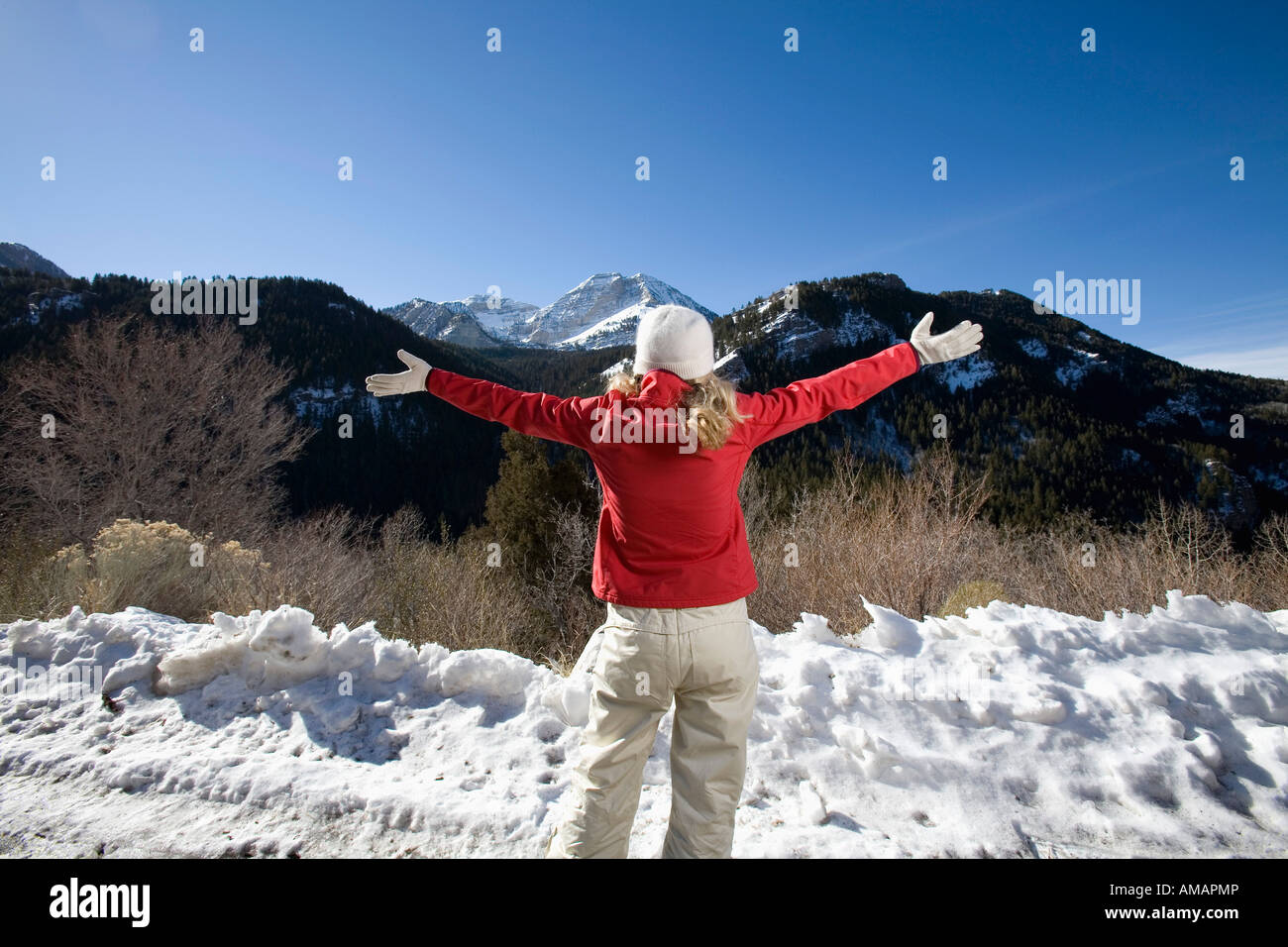 A woman looking at the mountains with her arms outstretched - Stock Image