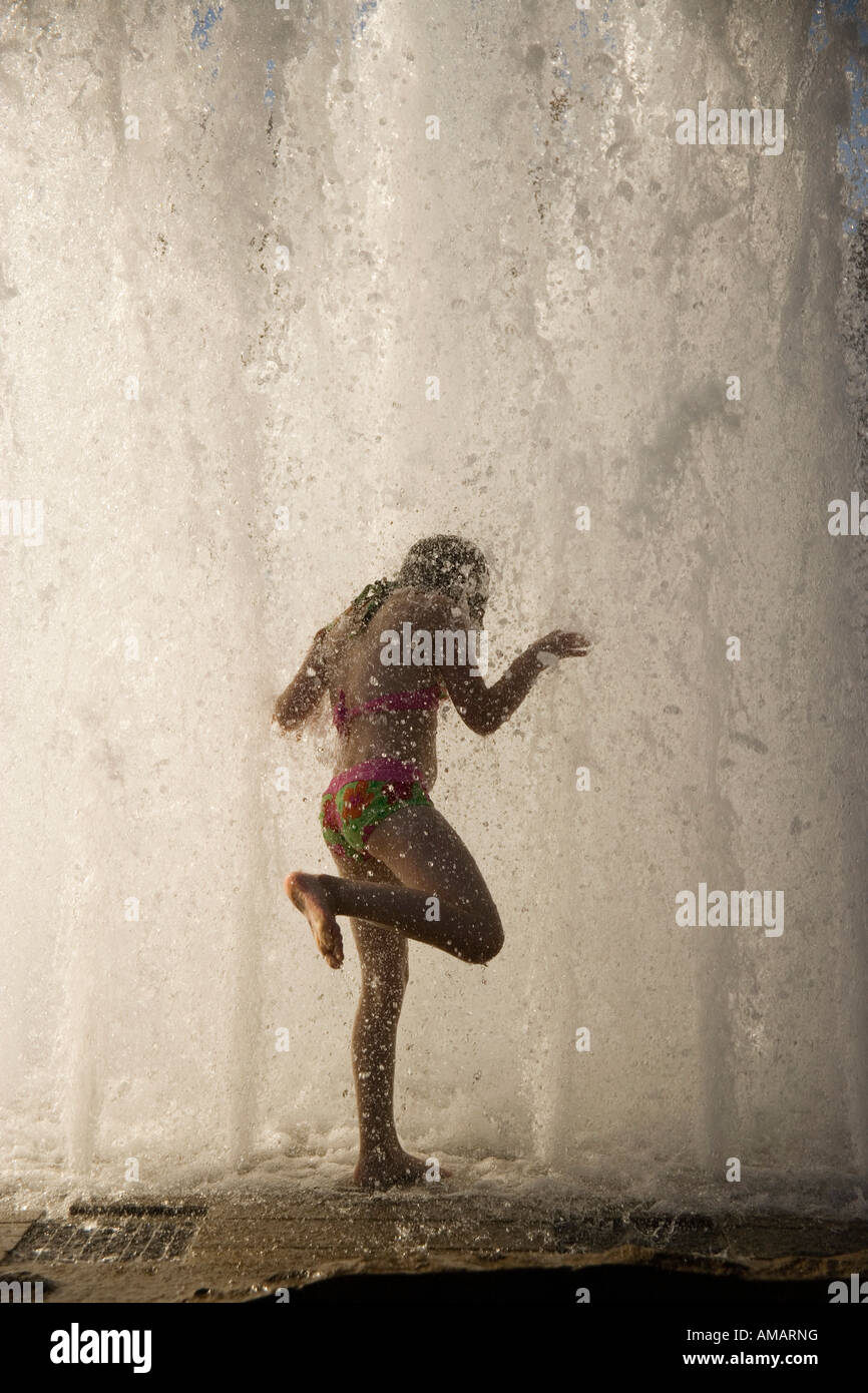 A woman standing underneath a waterfall - Stock Image