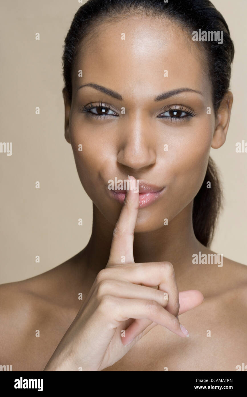 A woman putting her finger on her lips - Stock Image