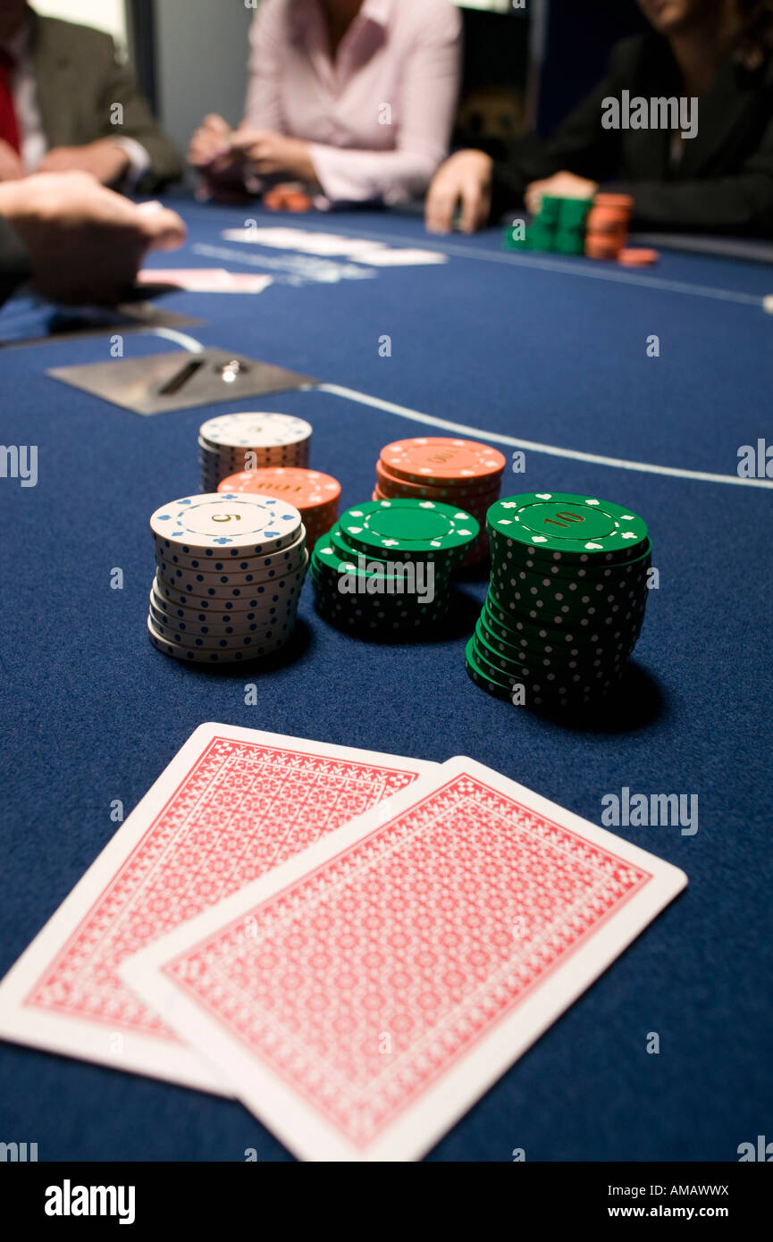 Playing cards and stacks of gambling chips on casino table - Stock Image