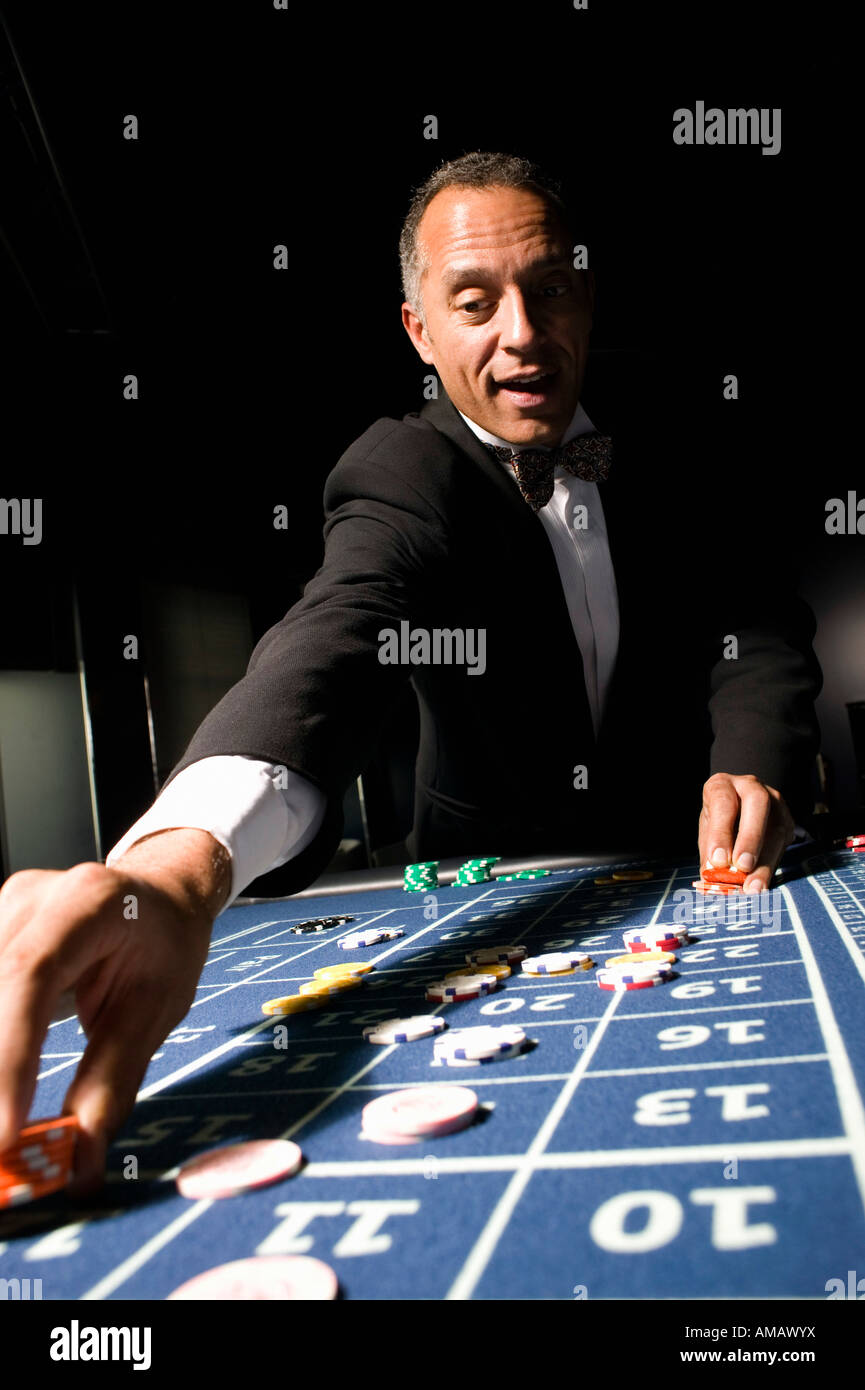 Well dressed man placing bet at roulette table - Stock Image