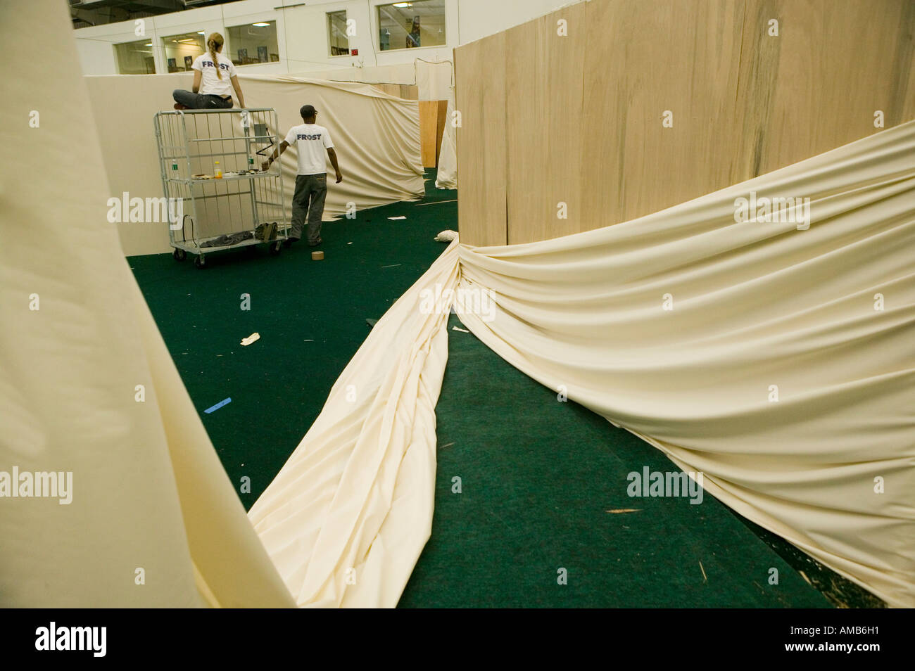 Setting up white drapes for an event 2005 - Stock Image