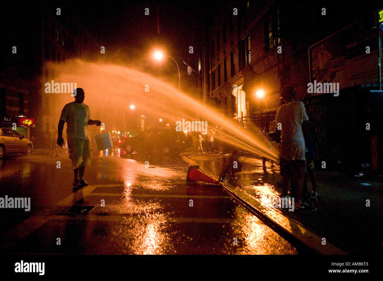Playing in the fire hydrant spray in Harlem New York City USA August 2005 - Stock Image