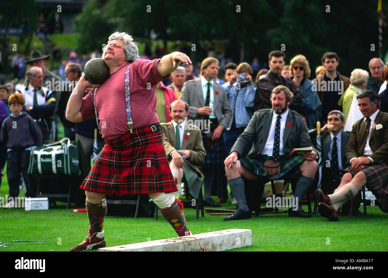 Scottish man wearing kilt putting the shot at Royal Braemar Gathering Highland Games near Balmoral, Grampian Region, Scotland - Stock Image