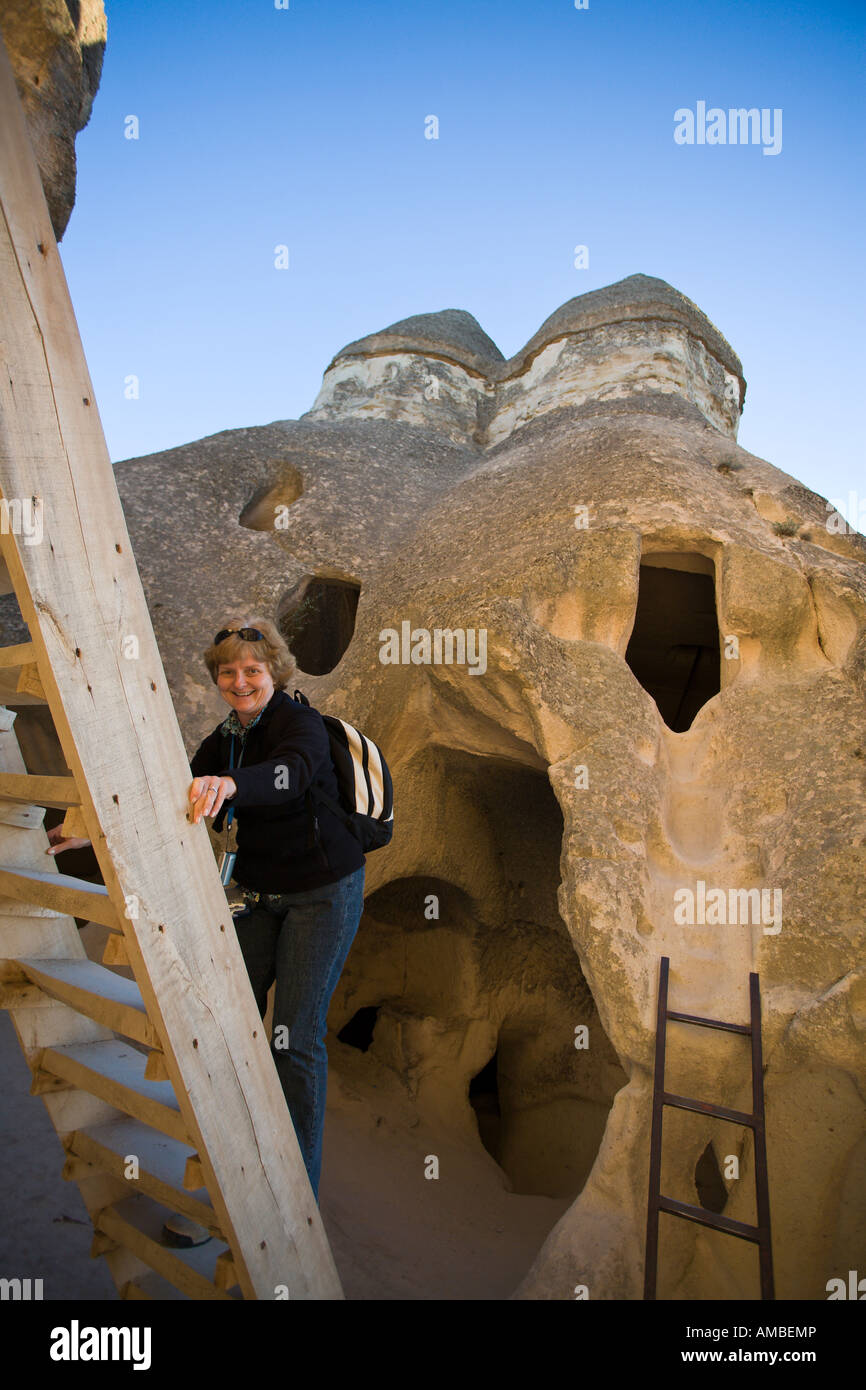 Going Up.  A middle aged woman wearing a backpack smiles as she climbs a ladder up to a troglodyte monastery chapel - Stock Image