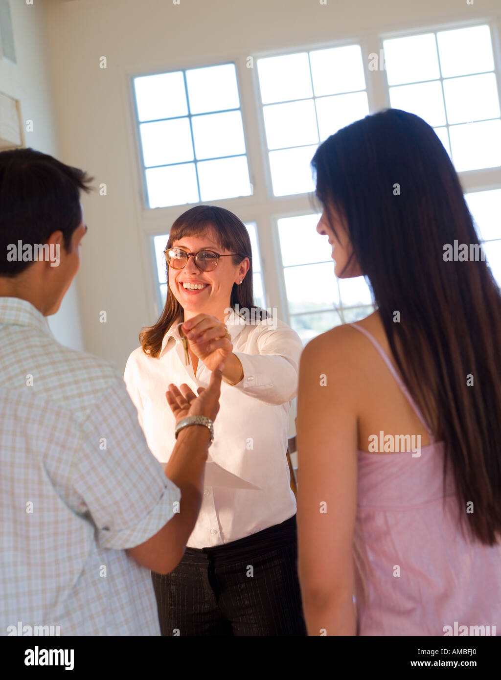 portrait of young hispanic couple at home holding their house keys Stock Photo