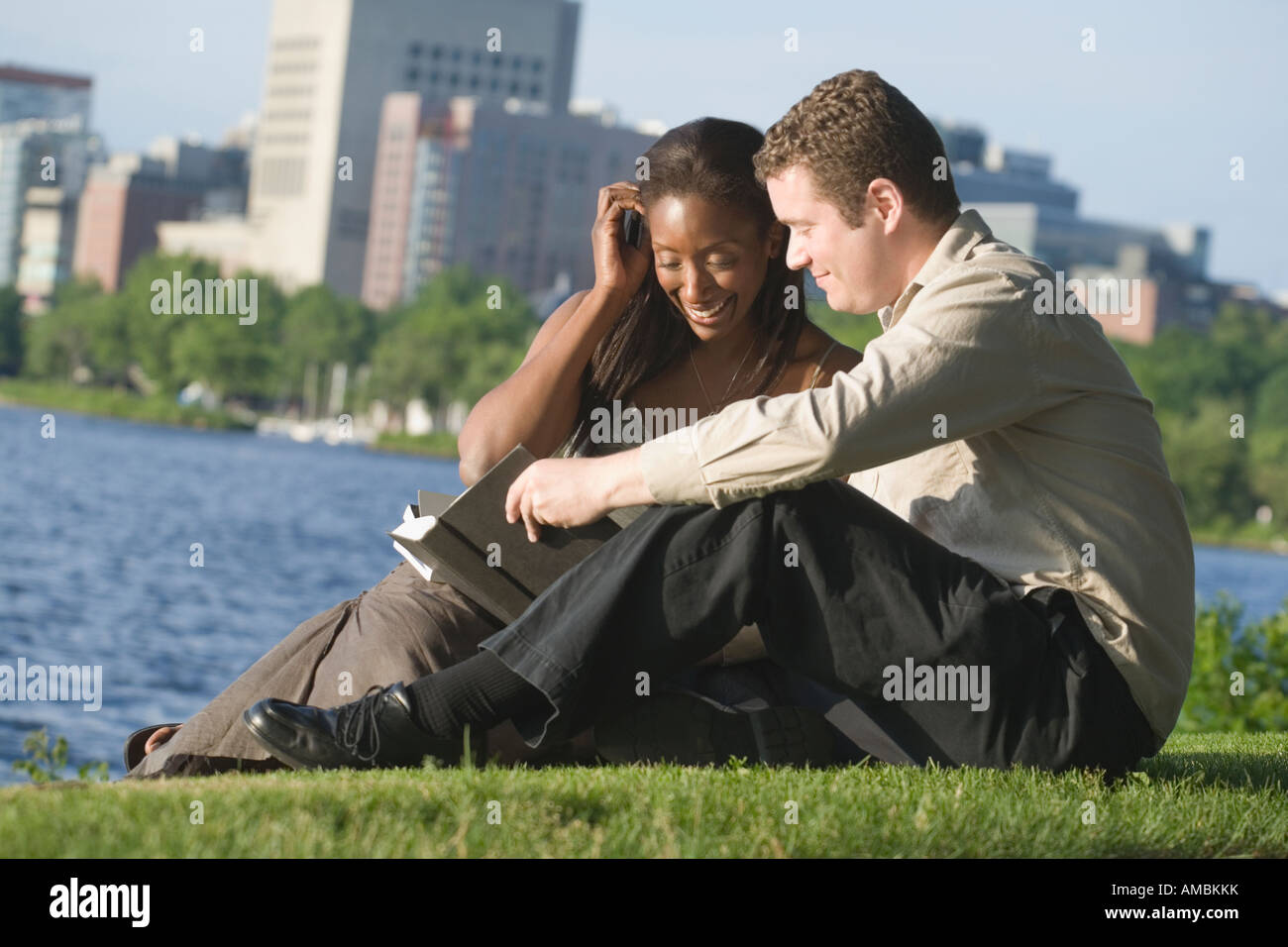 Mid adult couple sitting in a park reading a book, Boston, Massachusetts, USA Stock Photo