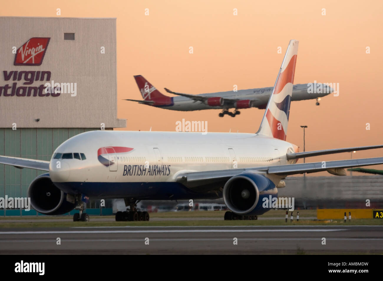 British airways boeing 777 taxiing for departure while virgin stock british airways boeing 777 taxiing for departure while virgin atlantic airbus a340 landing in the background heathrow airport uk publicscrutiny Image collections