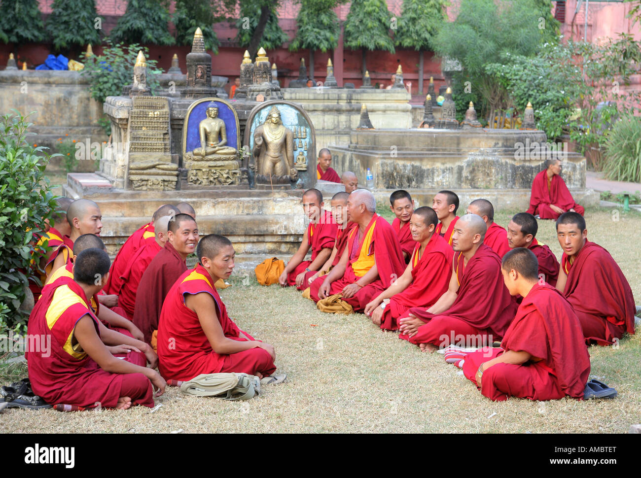 India, Bodhgaya: buddhist monks praying in the garden of Mahabodhi Temple, the place of the Buddha's Enlightenment - Stock Image