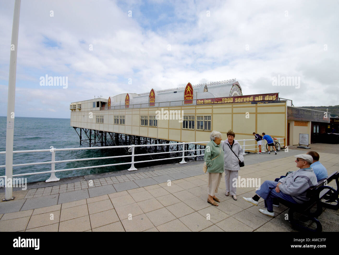 older people chat on the seafront of Aberystwyth with pier in background - Stock Image
