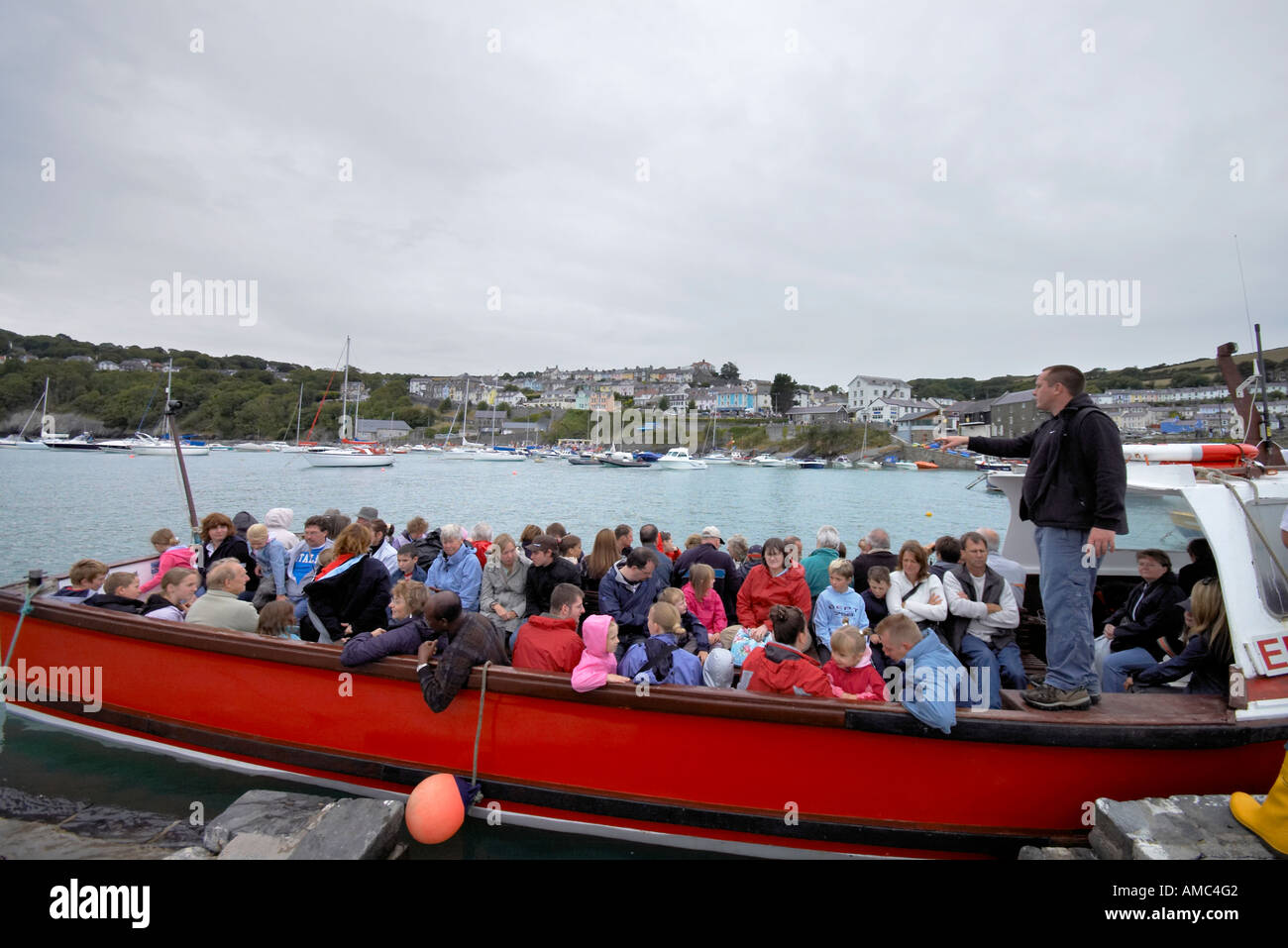 man counting people on a crowded whale watching boat at New Quay Wales - Stock Image