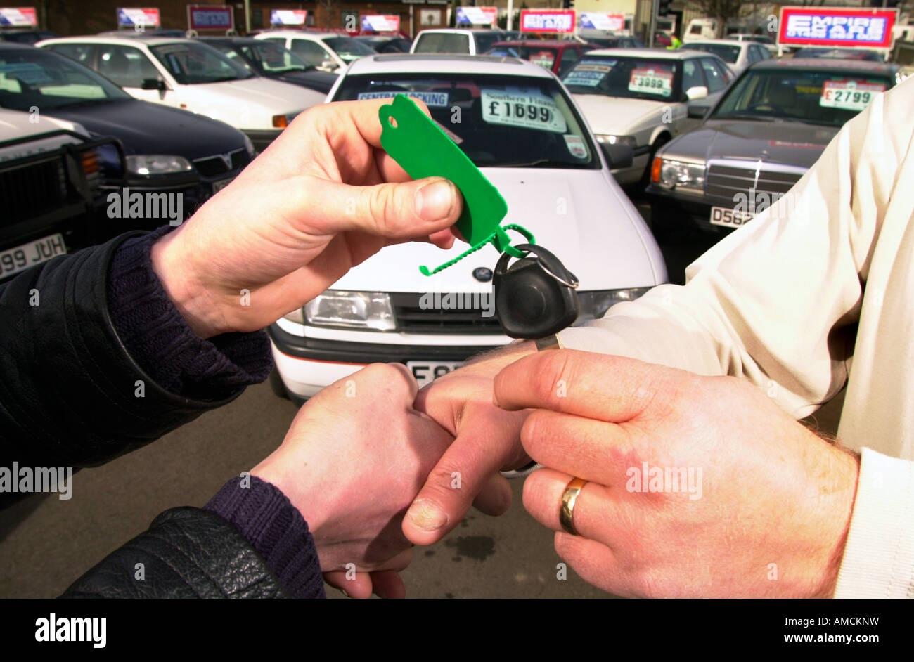 A DEAL IS SEALED WITH A HANDSHAKE AT A USED CAR DEALERSHIP UK - Stock Image