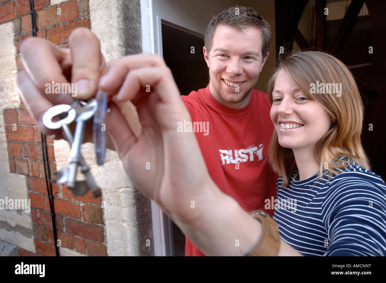 A YOUNG COUPLE MOVING INTO THEIR FIRST HOME WITH THEIR HOUSE KEYS UK - Stock Image