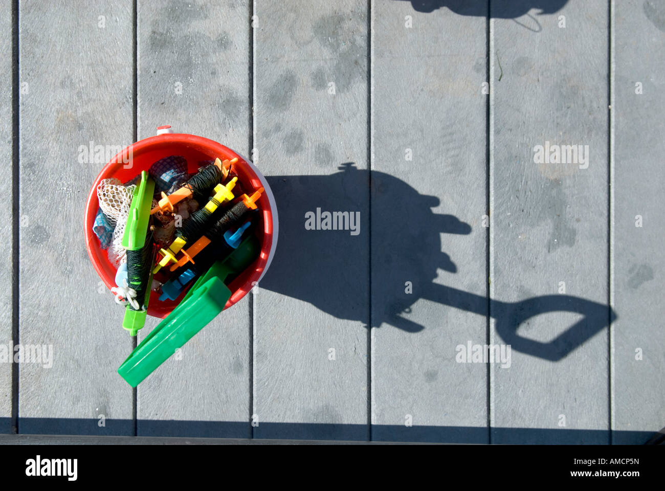 looking down at a toy bucket filled with several crab lines and a spade on a jetty in Cornwall - Stock Image