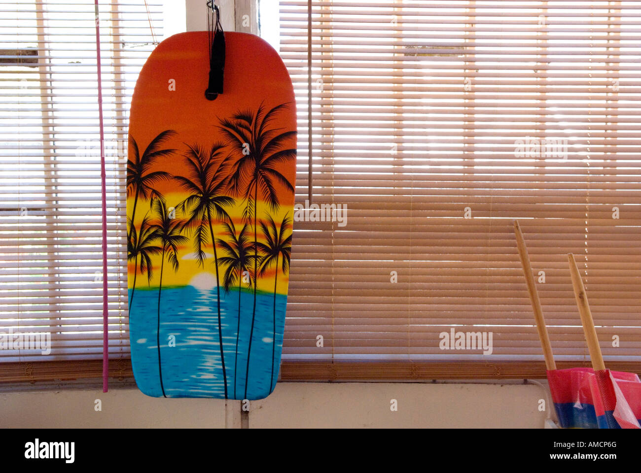 interior of beach house with wooden blind over window and body board with palm tree motif hanging against it - Stock Image
