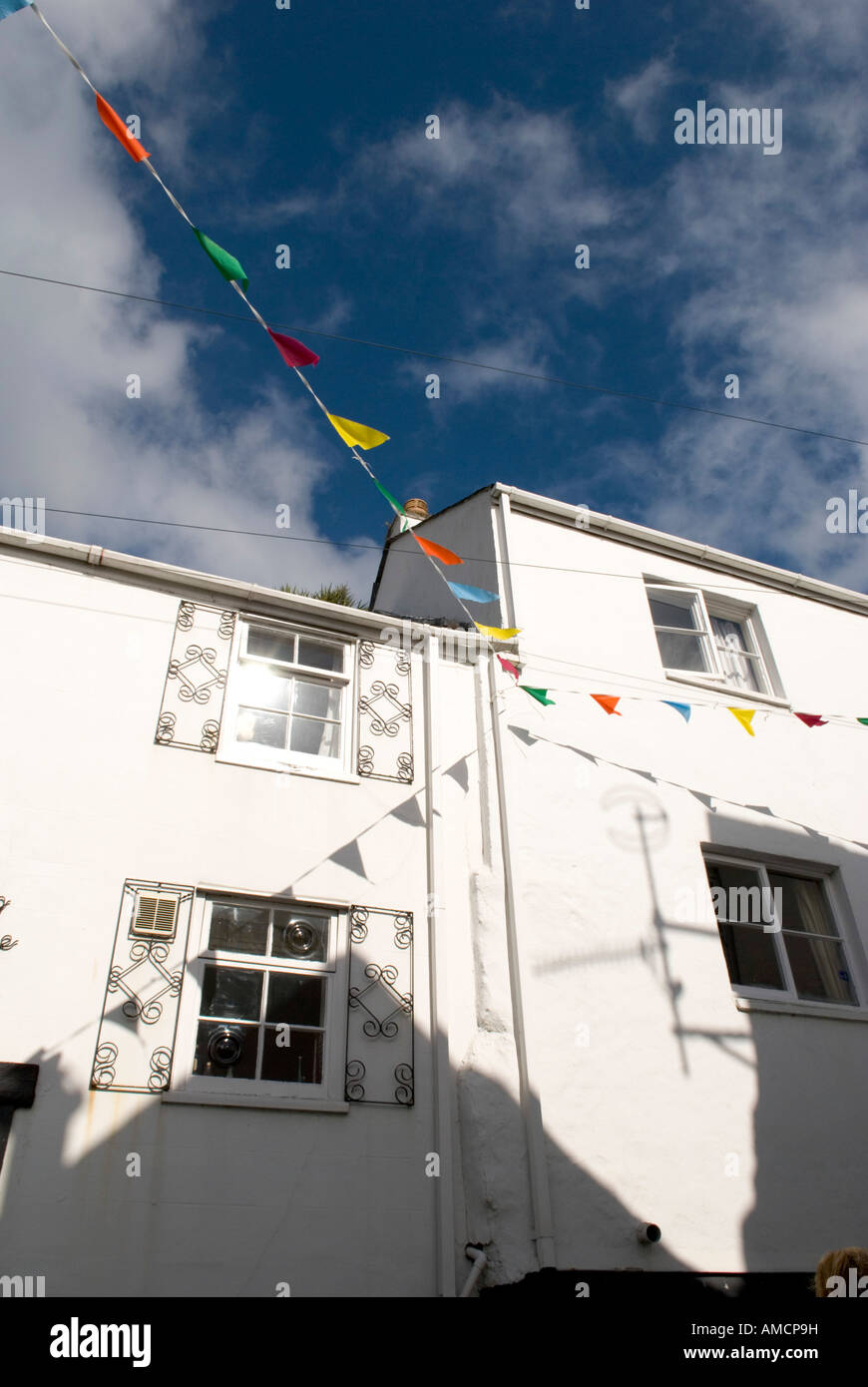 a typical cornish house with facade decorated with flags and buntings ona windy sunny day - Stock Image