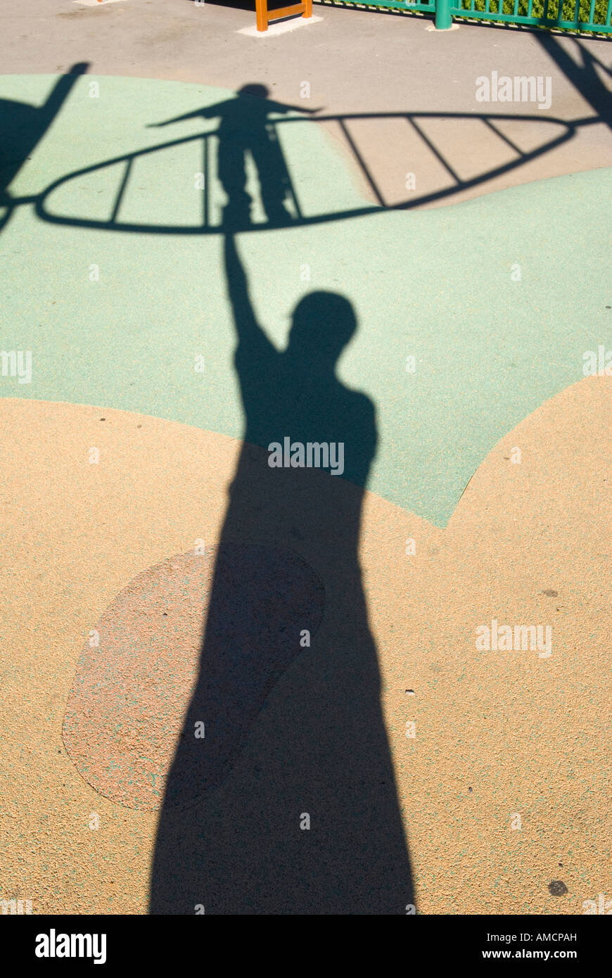 shadows of small child on climbing frame towering over shadow of adult on playground floor - Stock Image