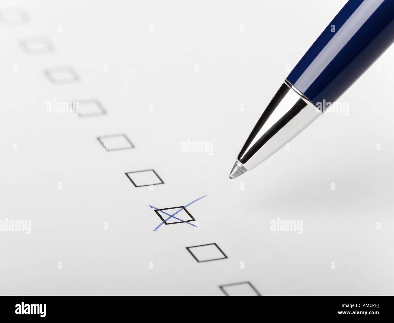 Pen writing X in tick box still life close up - Stock Image