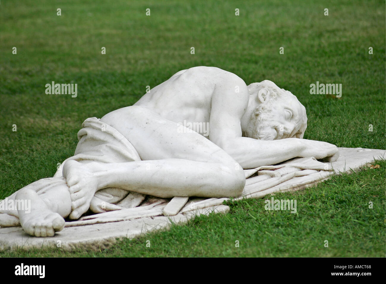 White marble sculpture of a semi clothed man lying on grass. Parham House a14d3671a