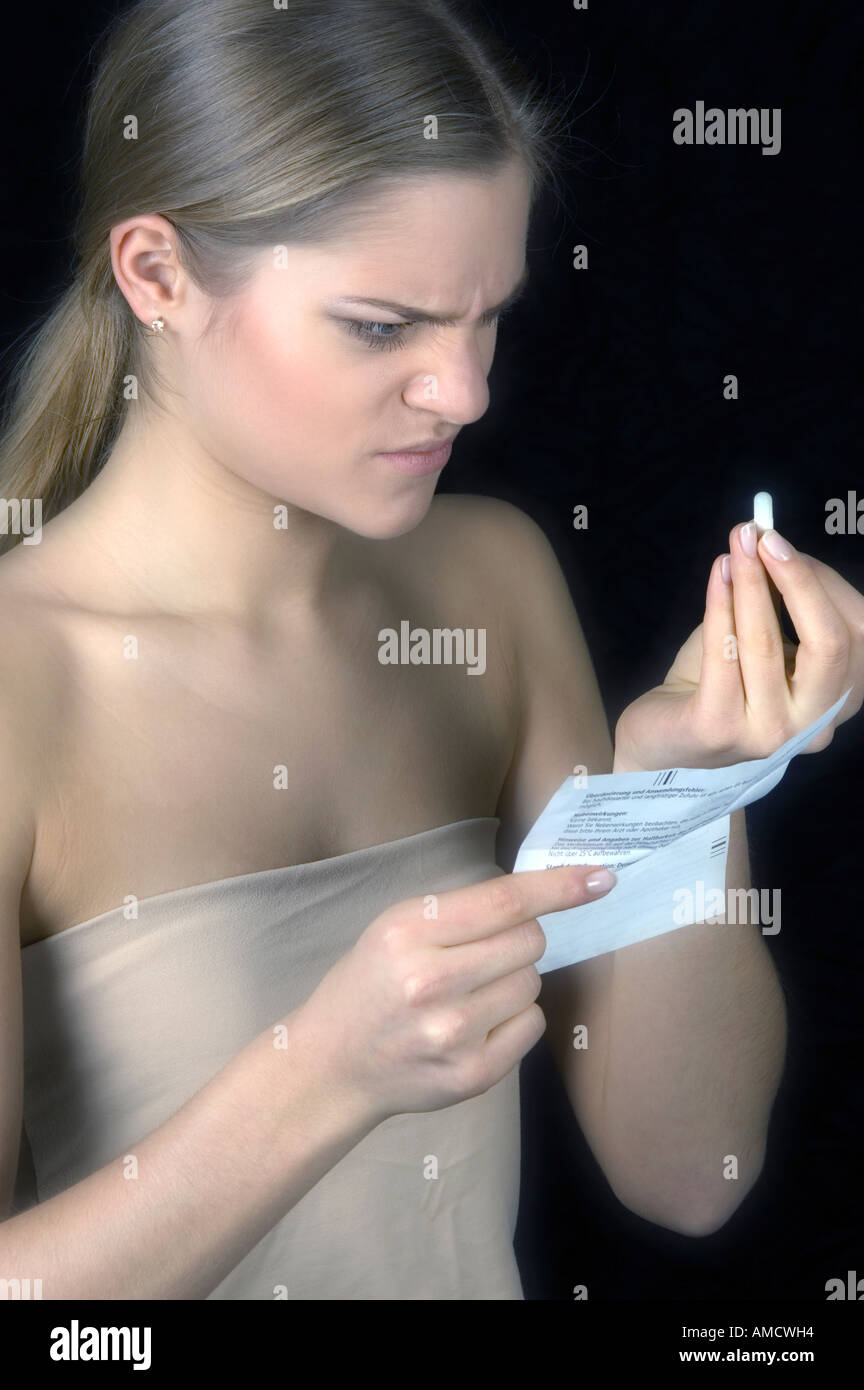 Woman taking pill and reading enclosing note Stock Photo