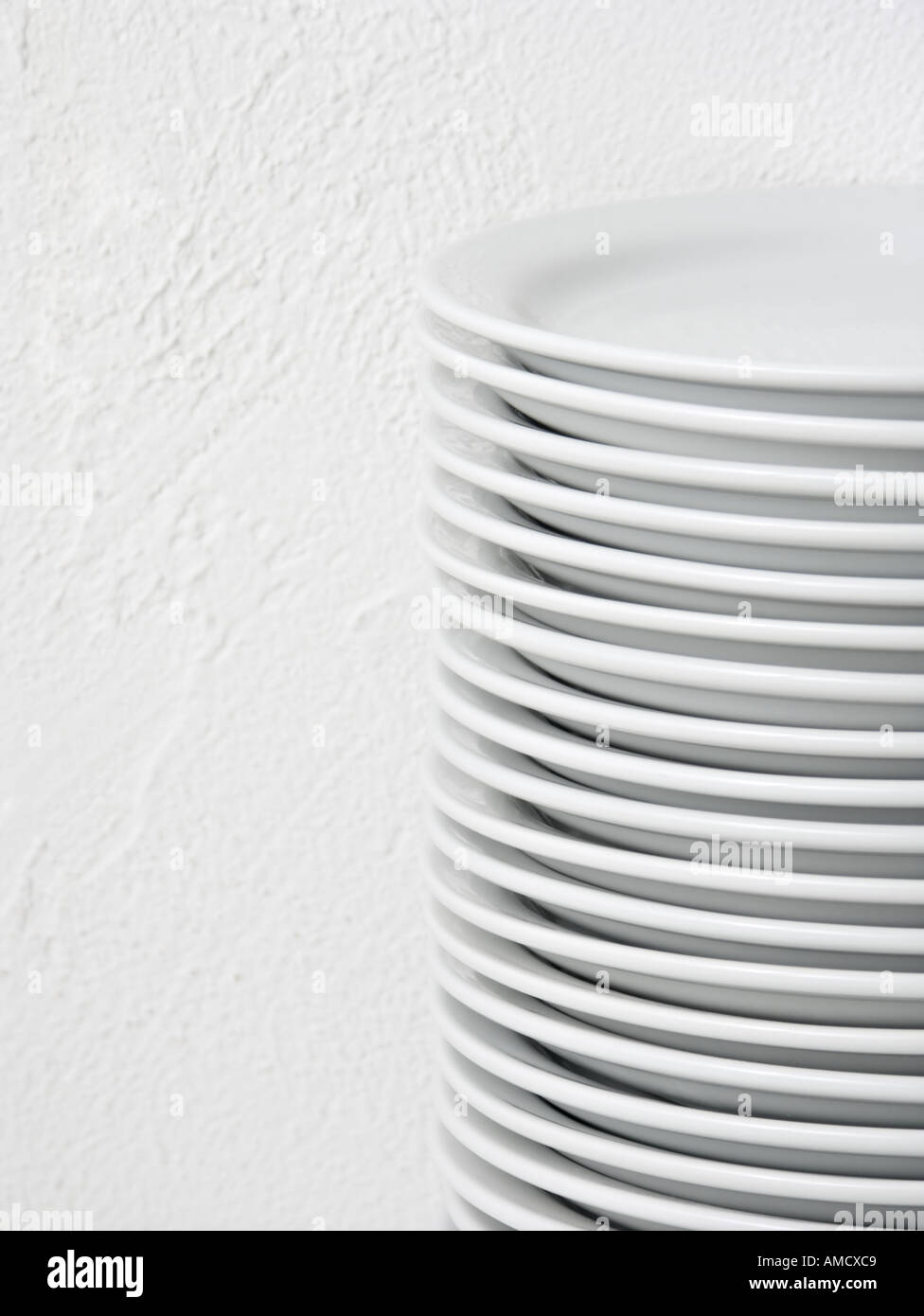 Stack of round white dinner plates on a white background - Stock Image