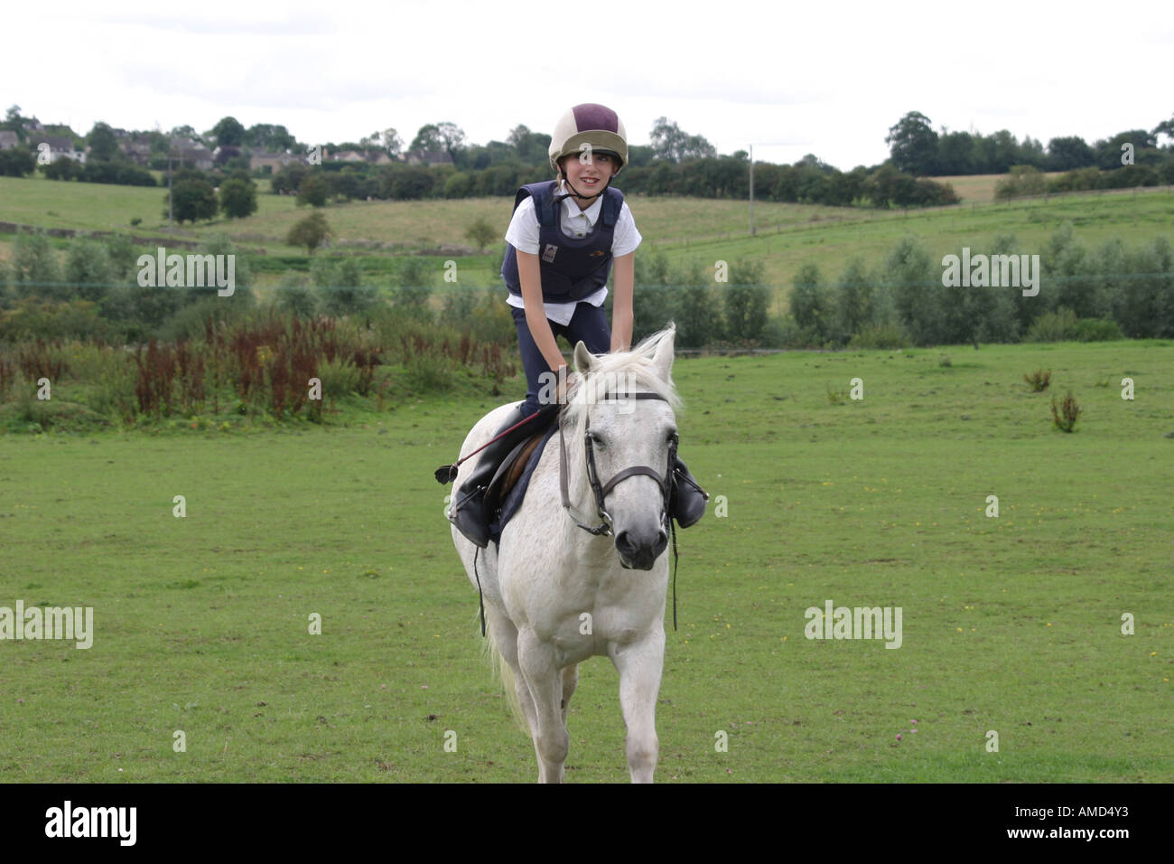 A young rider high in her saddle riding her pony. - Stock Image