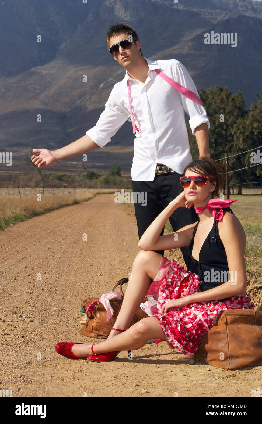 Couple Hitchhiking On Country Road Stock Photo