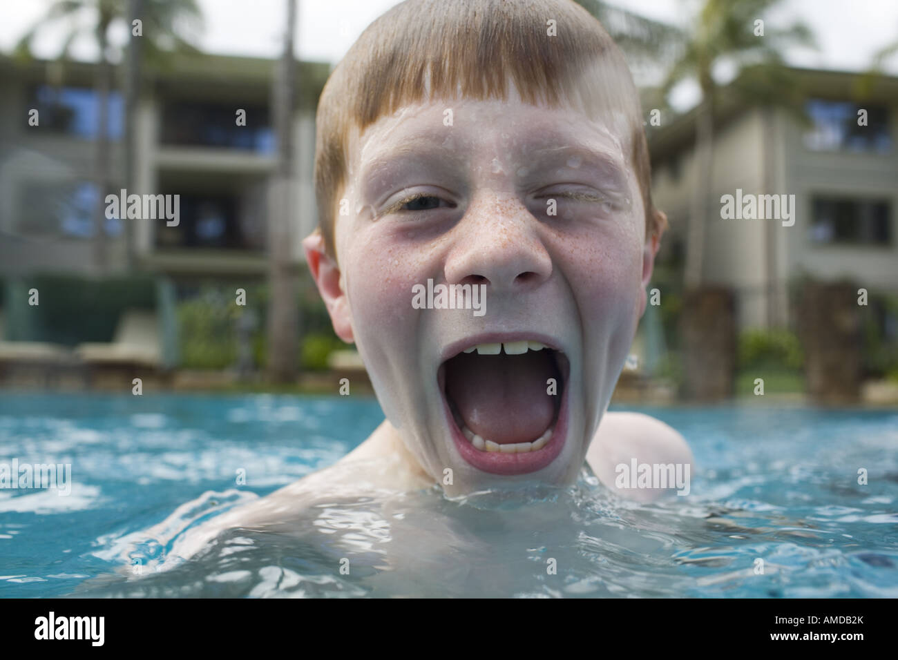 Boy in outdoor pool making funny face - Stock Image