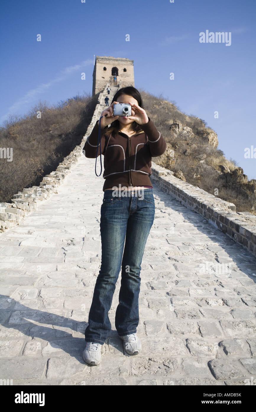 Woman facing camera taking photo Great Wall of China - Stock Image