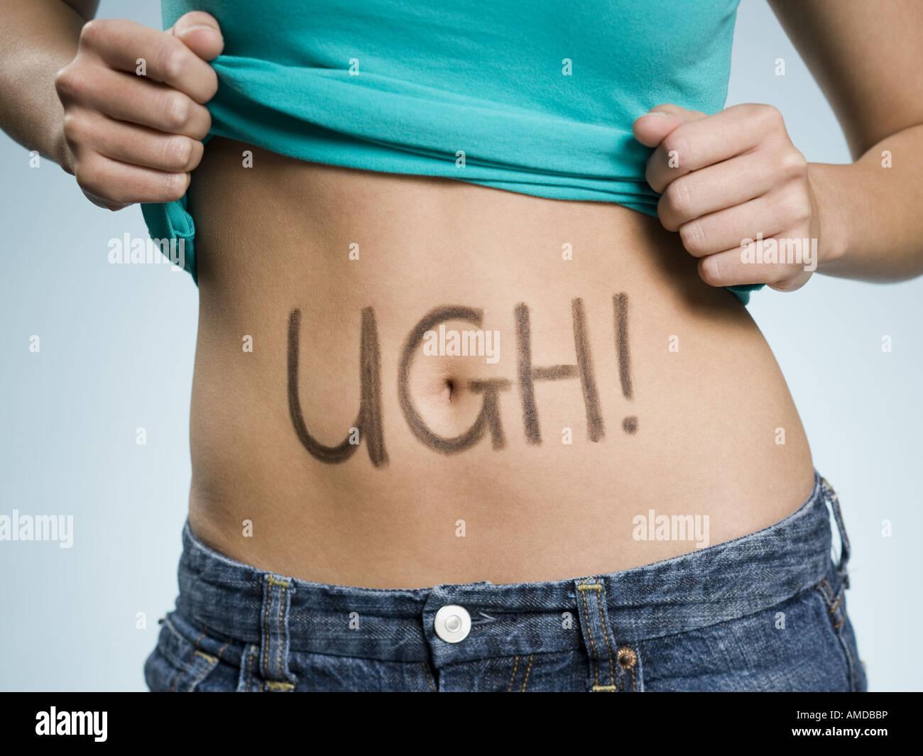 Female Abdomen with UGH! written on it - Stock Image