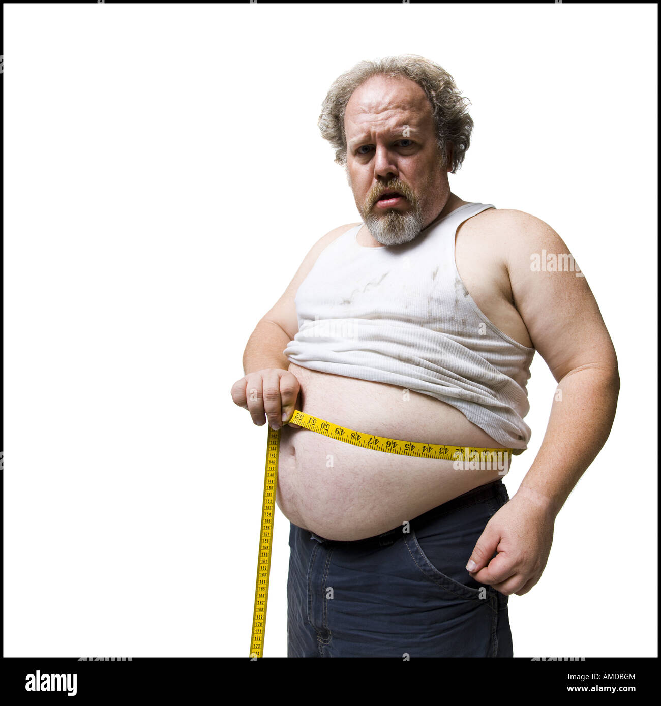 Obese man measuring waist with tape measure - Stock Image