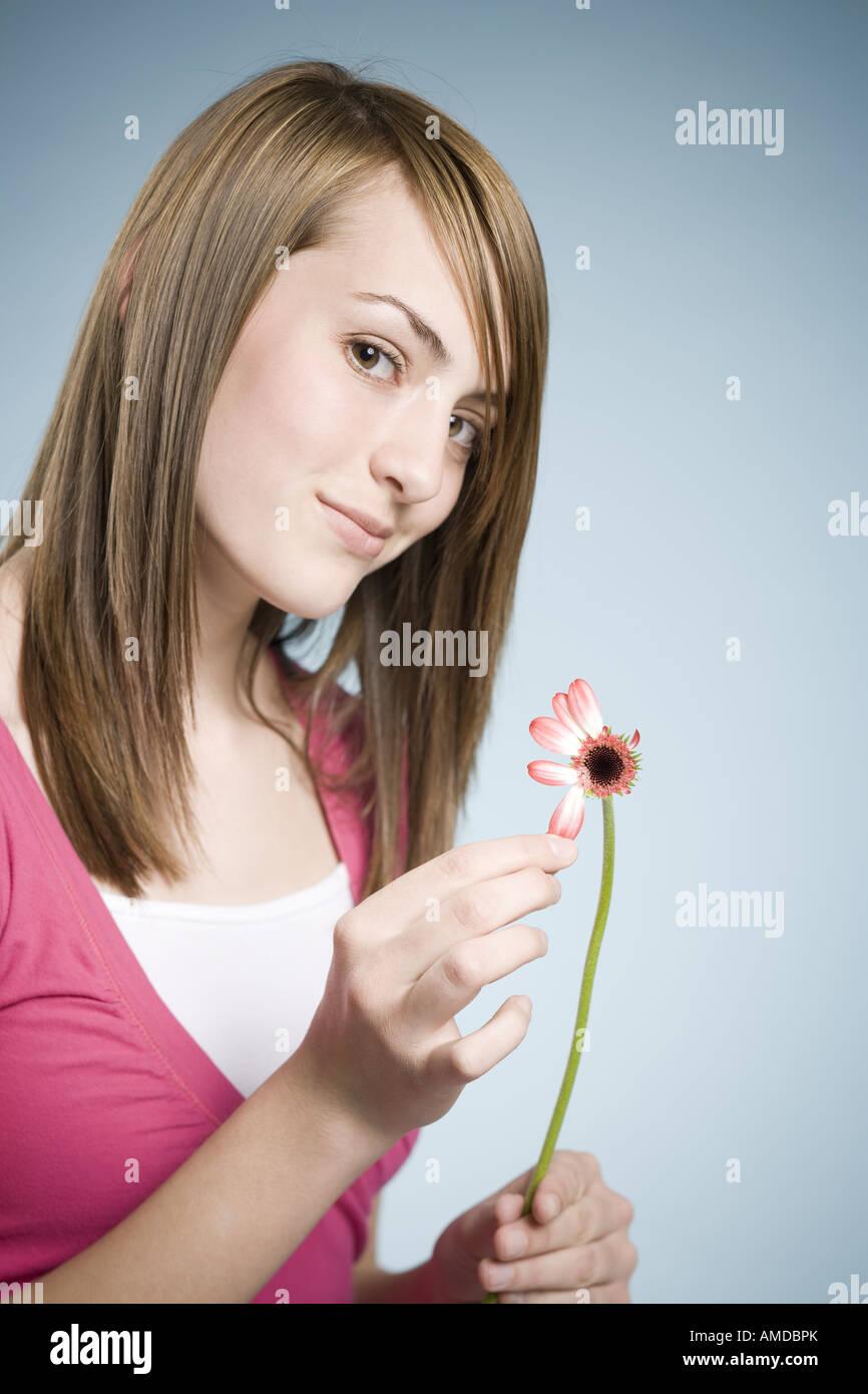 Girl picking petals off flower - Stock Image