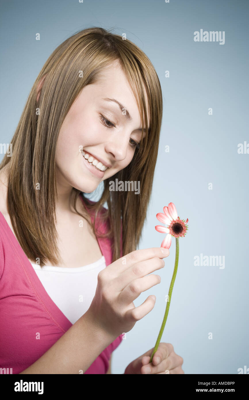 Girl picking petals off flower smiling - Stock Image