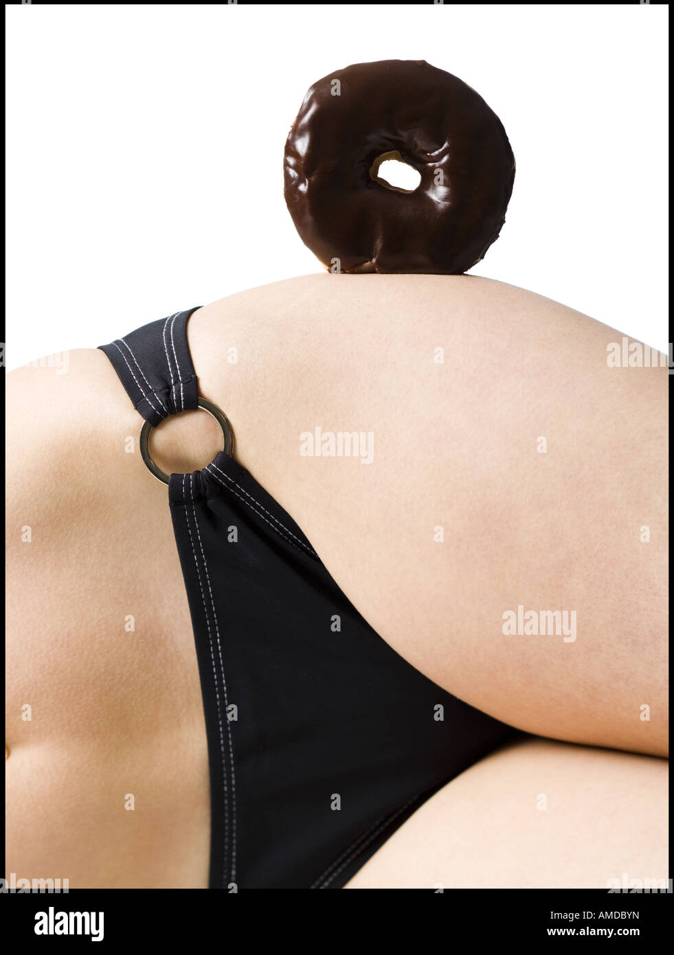 Detailed view of woman in bikini with donut on hip - Stock Image