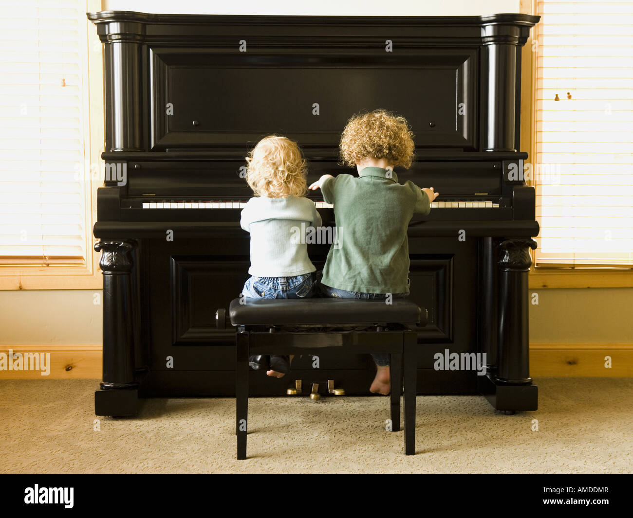 Rear view of two children sitting at upright piano Stock Photo